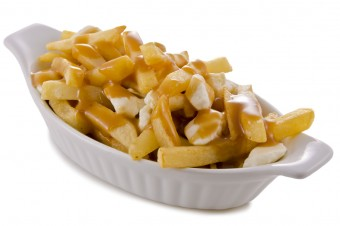 Poutine, traditional fast food in Quebec, Canada. Closeup.